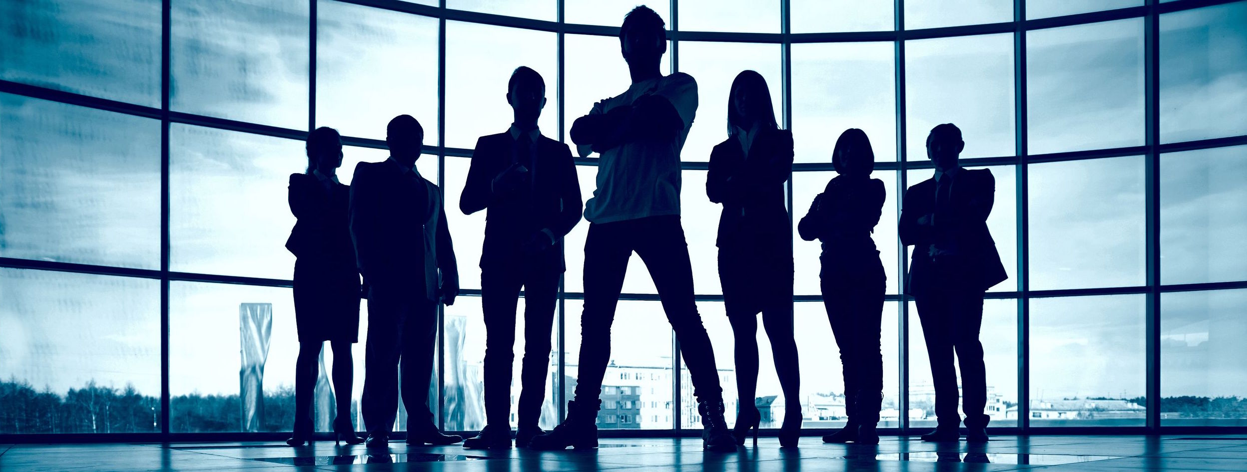 25891418 - business team standing against window with leader in front
