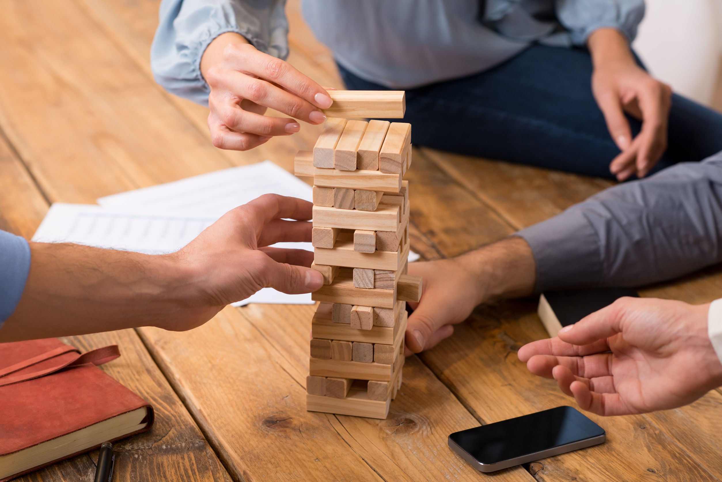 51077703 - close up of hands helping build a building of wooden pieces. businesspeople planning a new business strategy. business team trying to generate new ideas with the help of playing with wooden bricks. business risk concept.